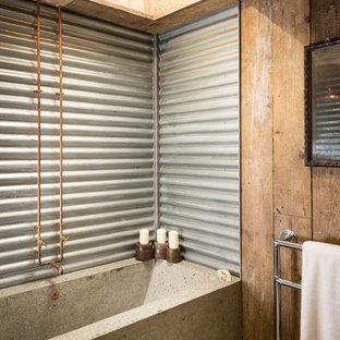 Ejemplo de cuarto de baño principal, rural, con suelo de cemento y bañera empotrada