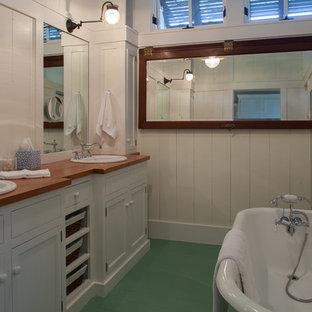 Modelo de cuarto de baño costero con lavabo encastrado, bañera exenta, encimera de madera, suelo verde y encimeras marrones
