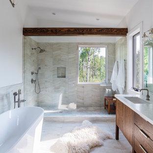 Modelo de cuarto de baño rural con armarios con paneles lisos, puertas de armario de madera en tonos medios, bañera exenta, ducha empotrada, baldosas y/o azulejos beige, paredes blancas, lavabo bajoencimera, suelo beige, ducha abierta y encimeras blancas