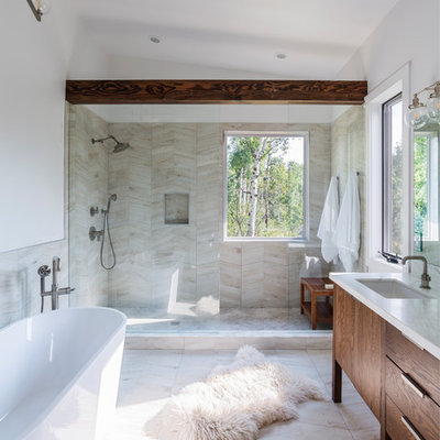 Example of a mountain style beige tile beige floor bathroom design in Denver with flat-panel cabinets, dark wood cabinets, white walls, an undermount sink and white countertops