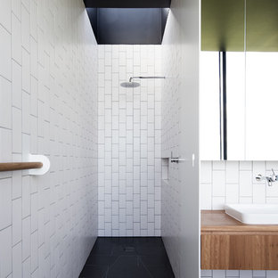 Inspiration for a contemporary 3/4 bathroom in Melbourne with flat-panel cabinets, medium wood cabinets, a curbless shower, white tile, subway tile, a drop-in sink, wood benchtops, black floor and an open shower.