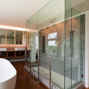 Foto de cuarto de baño principal, actual, grande, con armarios abiertos, puertas de armario de madera oscura, bañera exenta, ducha abierta, baldosas y/o azulejos amarillos, paredes blancas, suelo de bambú, lavabo sobreencimera y encimera de cuarzo compacto