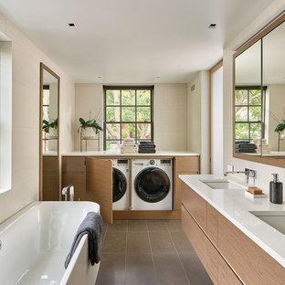 Réalisation d'une salle de bain principale minimaliste avec un placard à porte plane, des portes de placard en bois brun, une baignoire indépendante, un mur blanc, un lavabo encastré, un sol gris, un plan de toilette blanc, un WC suspendu, un plan de toilette en quartz modifié et buanderie.