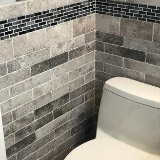 Imagen de cuarto de baño principal, moderno, de tamaño medio, con armarios con rebordes decorativos, puertas de armario negras, bañera empotrada, ducha empotrada, sanitario de una pieza, baldosas y/o azulejos grises, baldosas y/o azulejos de cerámica, paredes grises, suelo de baldosas de cerámica, lavabo tipo consola, encimera de vidrio, suelo gris y ducha con cortina
