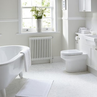 Inspiration for a large contemporary bathroom in Hertfordshire with a built-in sink, beaded cabinets, white cabinets, a claw-foot bath, a one-piece toilet, white tiles, white walls and mosaic tile flooring.