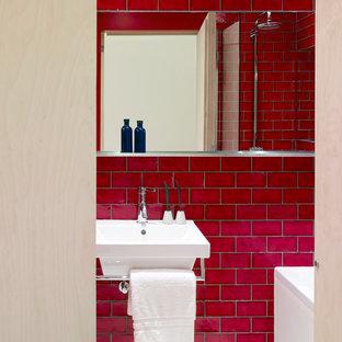 Imagen de cuarto de baño infantil, actual, con bañera encastrada, ducha esquinera, sanitario de pared, baldosas y/o azulejos rojos, baldosas y/o azulejos de cerámica, paredes rojas, lavabo suspendido, suelo blanco y ducha con puerta con bisagras