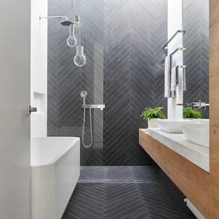 Идея дизайна: маленькая главная ванная комната в современном стиле с плоскими фасадами, фасадами цвета дерева среднего тона, отдельно стоящей ванной, открытым душем, раздельным унитазом, черной плиткой, керамогранитной плиткой, полом из керамогранита, настольной раковиной, мраморной столешницей, черным полом, открытым душем и черными стенами