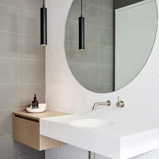 Inspiration for a modern bathroom in Melbourne with flat-panel cabinets, light wood cabinets, white walls, a wall-mount sink and grey floor.