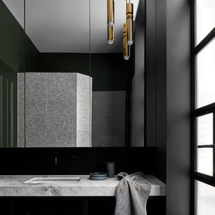 Photo of a medium sized contemporary ensuite bathroom in Melbourne with open cabinets, medium wood cabinets, an alcove shower, black tiles, metal tiles, black walls, cement flooring, a submerged sink, marble worktops, grey floors, an open shower and grey worktops.