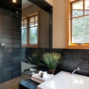 Esempio di una stanza da bagno padronale tradizionale di medie dimensioni con ante in legno chiaro, vasca da incasso, doccia doppia, piastrelle nere, piastrelle in pietra e pavimento con piastrelle di ciottoli