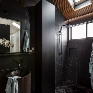 This is an example of a mid-sized contemporary 3/4 bathroom in Sydney with black cabinets, an open shower, black tile, black walls, an integrated sink, black floor, black benchtops, a niche, a single vanity and a freestanding vanity.