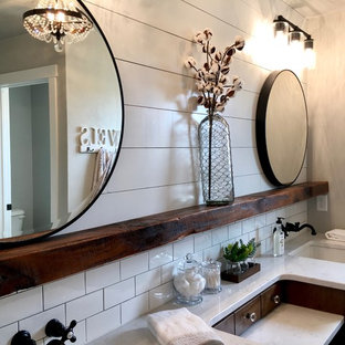 Inspiration for a mid-sized country master bathroom in Other with furniture-like cabinets, dark wood cabinets, an alcove shower, a one-piece toilet, grey walls, ceramic floors, a drop-in sink, marble benchtops, black floor and a hinged shower door.