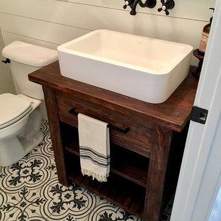 Foto de cuarto de baño con ducha, campestre, pequeño, con armarios abiertos, puertas de armario de madera en tonos medios, sanitario de una pieza, paredes grises, suelo con mosaicos de baldosas, lavabo de seno grande, encimera de madera, suelo negro y encimeras marrones