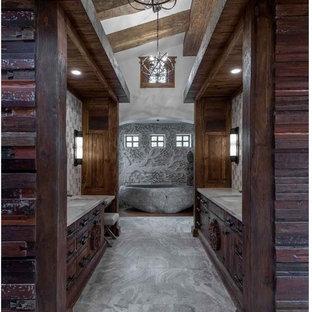 Idee per una grande stanza da bagno padronale etnica con ante lisce, ante in legno bruno, vasca giapponese, piastrelle in pietra, pavimento con piastrelle in ceramica e top in superficie solida