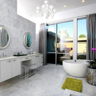 Minimalist gray tile freestanding bathtub photo in New Orleans with an undermount sink, flat-panel cabinets and white cabinets