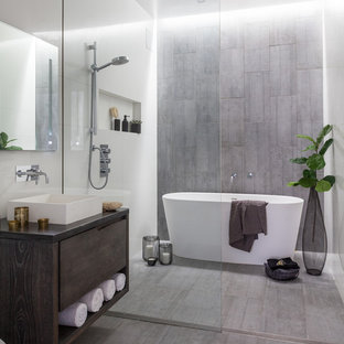 Diseño de cuarto de baño principal, industrial, pequeño, sin sin inodoro, con bañera exenta, baldosas y/o azulejos grises, baldosas y/o azulejos de porcelana, paredes blancas, suelo de baldosas de porcelana, lavabo sobreencimera, encimera de zinc, suelo gris, ducha abierta, encimeras grises, armarios con paneles lisos y puertas de armario de madera en tonos medios
