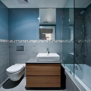 Idee per una stanza da bagno per bambini design con lavabo sospeso, ante lisce, ante in legno chiaro, top in saponaria, vasca da incasso, doccia aperta, WC sospeso, piastrelle grigie, piastrelle in gres porcellanato, pareti blu e pavimento in gres porcellanato