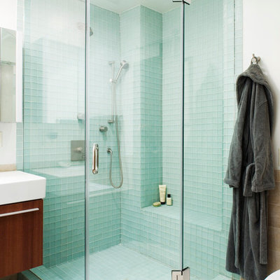 Mid-sized eclectic master blue tile and glass tile ceramic tile bathroom photo in New York with flat-panel cabinets, dark wood cabinets, white walls, a wall-mount sink and solid surface countertops