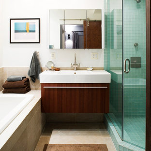 Inspiration for a mid-sized eclectic master blue tile and glass tile ceramic floor bathroom remodel in New York with a wall-mount sink, flat-panel cabinets, dark wood cabinets, white walls and solid surface countertops