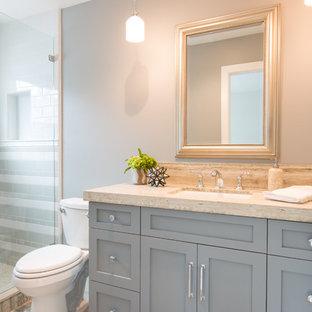 Ispirazione per una piccola stanza da bagno stile marinaro con ante con riquadro incassato, ante grigie, vasca/doccia, WC monopezzo, piastrelle beige, piastrelle in ceramica, pareti blu, pavimento in travertino, lavabo sottopiano e top in pietra calcarea