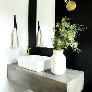 Immagine di una piccola stanza da bagno con doccia minimal con consolle stile comò, ante in legno scuro, pareti nere, pavimento in gres porcellanato, lavabo integrato, top in legno, pavimento marrone, top marrone, un lavabo e mobile bagno sospeso