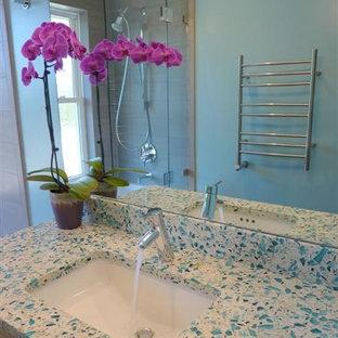 Ejemplo de cuarto de baño infantil, actual, pequeño, con lavabo bajoencimera, armarios con paneles lisos, puertas de armario de madera clara, encimera de vidrio reciclado, bañera empotrada, combinación de ducha y bañera, sanitario de dos piezas, baldosas y/o azulejos grises, baldosas y/o azulejos de porcelana, paredes azules y suelo de baldosas de porcelana