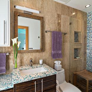 Foto de cuarto de baño tropical, de tamaño medio, con armarios con paneles lisos, puertas de armario de madera en tonos medios, ducha a ras de suelo, sanitario de una pieza, baldosas y/o azulejos negros, baldosas y/o azulejos azules, baldosas y/o azulejos verdes, baldosas y/o azulejos multicolor, baldosas y/o azulejos en mosaico, paredes marrones, lavabo bajoencimera y encimera de vidrio reciclado