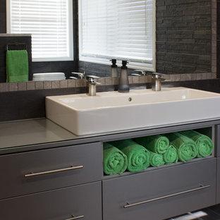 Esempio di una piccola stanza da bagno padronale minimal con ante lisce, ante grigie, doccia aperta, piastrelle grigie, piastrelle in pietra, pareti grigie, pavimento in gres porcellanato, lavabo rettangolare e top in vetro
