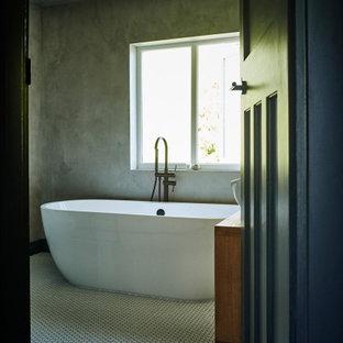 Ejemplo de cuarto de baño infantil, minimalista, de tamaño medio, con armarios tipo mueble, puertas de armario de madera oscura, bañera exenta, ducha abierta, sanitario de una pieza, paredes grises, suelo con mosaicos de baldosas, lavabo sobreencimera, suelo amarillo y ducha abierta