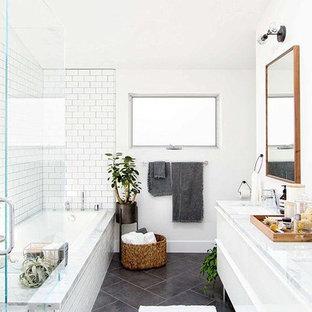 Идея дизайна: ванная комната в скандинавском стиле с плоскими фасадами, белыми фасадами, ванной в нише, угловым душем, белой плиткой, плиткой кабанчик, белыми стенами, полом из сланца, врезной раковиной, мраморной столешницей, серым полом и душем с распашными дверями