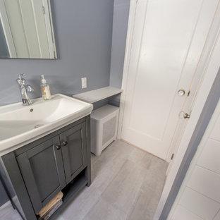Foto på ett litet funkis badrum, med ett nedsänkt handfat, luckor med infälld panel, grå skåp, bänkskiva i akrylsten, ett badkar i en alkov, en dusch i en alkov, en toalettstol med hel cisternkåpa, vit kakel, porslinskakel, grå väggar och klinkergolv i porslin