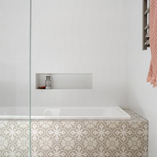 This is an example of a mediterranean bathroom in Perth with a drop-in tub, beige tile, white tile and white walls.