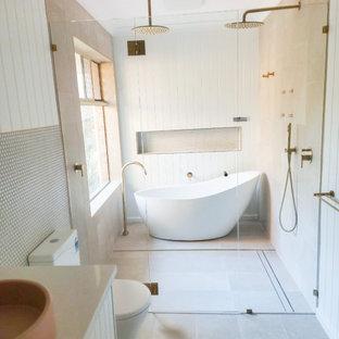 Inredning av ett modernt stort grå grått en-suite badrum, med skåp i shakerstil, vita skåp, ett fristående badkar, våtrum, en toalettstol med hel cisternkåpa, vit kakel, kakel i småsten, vita väggar, klinkergolv i porslin, ett fristående handfat, granitbänkskiva, grått golv och dusch med gångjärnsdörr