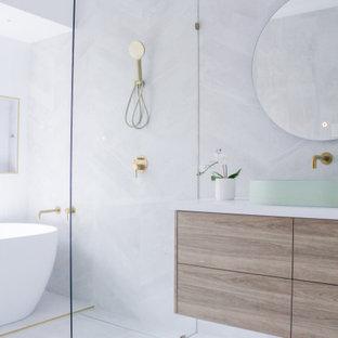 Idéer för mellanstora funkis vitt badrum för barn, med släta luckor, skåp i mörkt trä, ett fristående badkar, våtrum, grå kakel, porslinskakel, grå väggar, klinkergolv i porslin, ett fristående handfat, bänkskiva i kvarts, grått golv och med dusch som är öppen