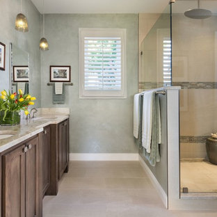 Mid-sized transitional master beige tile and porcelain tile porcelain tile corner shower photo in Miami with shaker cabinets, medium tone wood cabinets, green walls, an undermount sink and limestone countertops