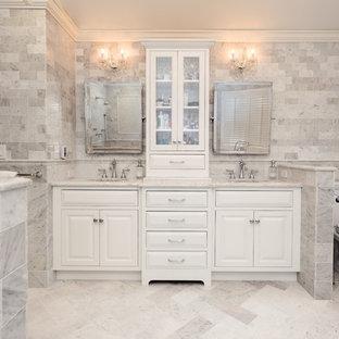 Inredning av ett klassiskt stort en-suite badrum, med ett undermonterad handfat, vita skåp, marmorbänkskiva, ett fristående badkar, en hörndusch, en toalettstol med separat cisternkåpa, vit kakel, stenkakel, grå väggar, marmorgolv och luckor med profilerade fronter