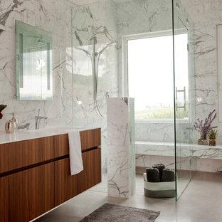 Idee per una grande stanza da bagno padronale minimal con ante lisce, ante in legno bruno, doccia a filo pavimento, piastrelle bianche, piastrelle grigie, vasca da incasso, lastra di pietra, pareti bianche, pavimento in cemento, lavabo integrato, top in superficie solida e top bianco