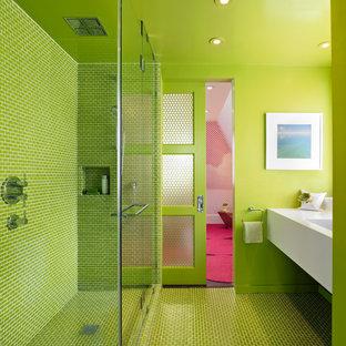 Modelo de cuarto de baño actual con puertas de armario blancas, ducha esquinera, baldosas y/o azulejos verdes, paredes verdes, lavabo integrado, suelo verde, ducha con puerta con bisagras y encimeras blancas