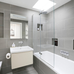 Large contemporary shower room bathroom in London with grey tiles, flat-panel cabinets, beige cabinets, an alcove bath, a shower/bath combination, a wall mounted toilet, grey walls, a wall-mounted sink, grey floors, a hinged door and white worktops.