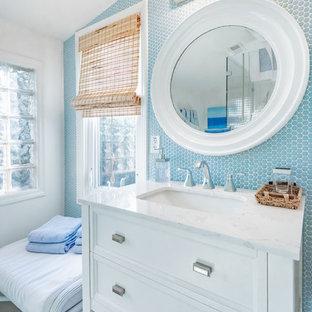 Ejemplo de cuarto de baño costero con armarios con paneles empotrados, puertas de armario blancas, baldosas y/o azulejos azules, baldosas y/o azulejos en mosaico, paredes blancas, lavabo bajoencimera, suelo gris y encimeras blancas