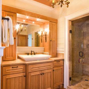 Esempio di una stanza da bagno padronale tradizionale con lavabo a bacinella, ante con riquadro incassato, ante in legno scuro, top in pietra calcarea, piastrelle beige, piastrelle in pietra, pareti bianche e pavimento in legno massello medio