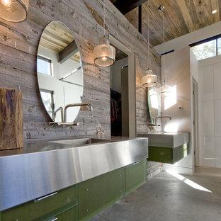 Ejemplo de cuarto de baño de estilo de casa de campo con lavabo integrado, armarios con paneles lisos, puertas de armario verdes, encimera de acero inoxidable y suelo de cemento