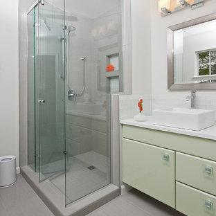 Immagine di una stanza da bagno tradizionale con lavabo a bacinella, ante verdi, doccia alcova e piastrelle grigie