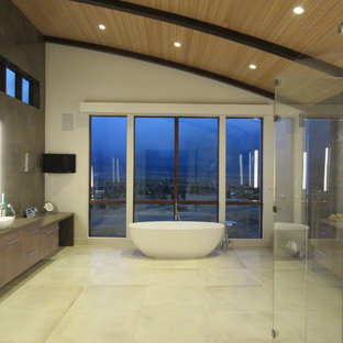 Huge minimalist master brown tile and marble tile porcelain tile and beige floor bathroom photo in Denver with flat-panel cabinets, medium tone wood cabinets, a one-piece toilet, brown walls, a vessel sink, marble countertops and a hinged shower door