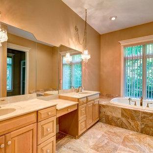 クリーブランドの広いトラディショナルスタイルのおしゃれなマスターバスルーム (一体型シンク、レイズドパネル扉のキャビネット、淡色木目調キャビネット、人工大理石カウンター、ドロップイン型浴槽、ベージュのタイル、セラミックタイル、ベージュの壁、セラミックタイルの床) の写真