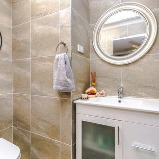 Idee per una piccola stanza da bagno con doccia moderna con lavabo integrato, ante di vetro, ante bianche, top in laminato, doccia ad angolo, WC monopezzo, piastrelle beige, pareti beige e pavimento con piastrelle di ciottoli