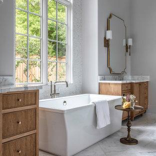 Ispirazione per un'ampia stanza da bagno padronale classica con vasca freestanding, piastrelle bianche, piastrelle di marmo, pavimento in marmo, top in marmo, pavimento bianco, top bianco, consolle stile comò, ante in legno scuro e pareti grigie