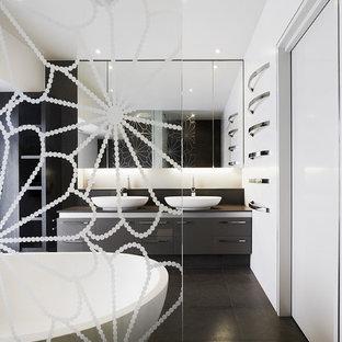 Foto de cuarto de baño contemporáneo, grande, con lavabo sobreencimera, armarios con paneles lisos, bañera exenta y baldosas y/o azulejos negros