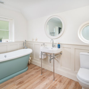 Traditional bathroom in Buckinghamshire with a one-piece toilet, white walls, light hardwood flooring, a console sink, beige floors, a single sink and wainscoting.