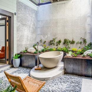 Ispirazione per una stanza da bagno tropicale con vasca freestanding, pareti grigie e pavimento grigio